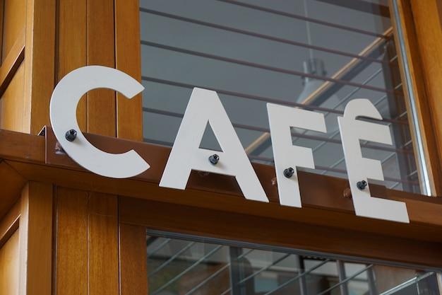 Close de uma placa de café fixada em uma viga de madeira de uma loja