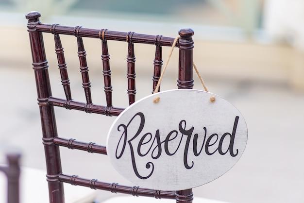 Close de uma placa reservada pendurada em uma cadeira em uma cerimônia de casamento