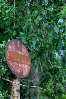 Close de uma placa vintage, descascada e enferrujada, em estado muito difícil, entre arbustos e árvores com folhas. conceito de velhice e abandono. copie o espaço para o site