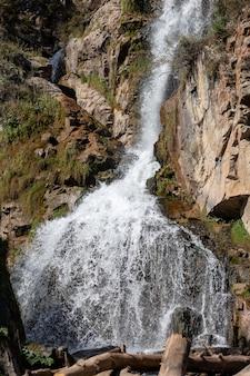 Close de uma poderosa cachoeira em alta qualidade. vista lateral de uma cachoeira ensolarada na natureza. um grande fluxo de água desce da montanha.