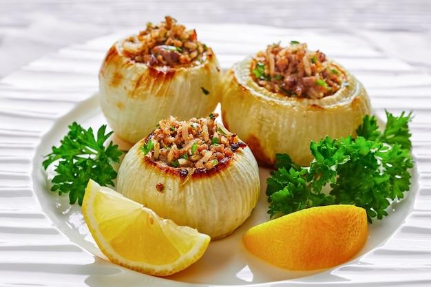 Close de uma porção de cebolas inteiras torradas caramelizadas recheadas com cordeiro picado e arroz em um prato com rodelas de limão, vista da paisagem