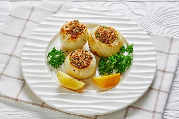 Close de uma porção de cebolas inteiras torradas caramelizadas recheadas com cordeiro picado e arroz em um prato sobre uma mesa de madeira branca, vista de cima