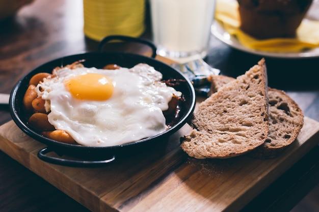 Close de uma refeição composta de ovo, torrada e feijão em uma placa de madeira