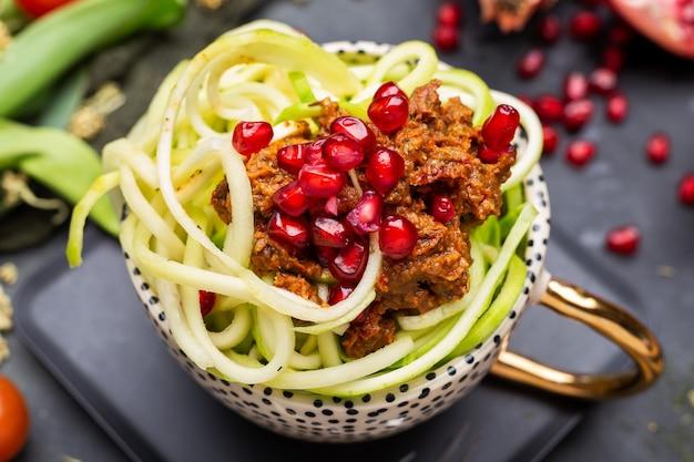 Close de uma refeição vegana com abobrinha em espiral, molho de tomate e romãs na xícara
