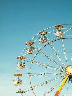 Close de uma roda-gigante multicolorida no parque de diversões