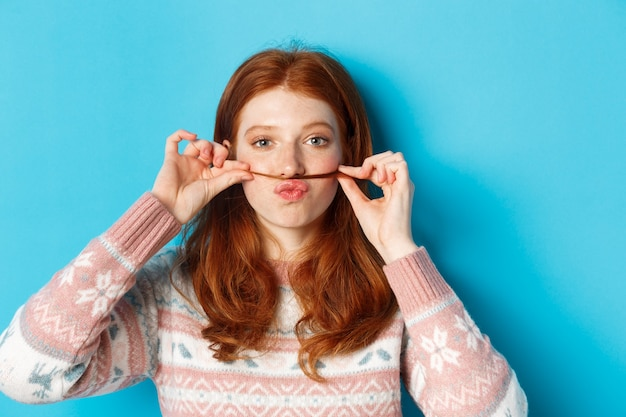 Close de uma ruiva boba e engraçada fazendo bigode com uma mecha de cabelo e lábios franzidos, fazendo uma careta contra um fundo azul
