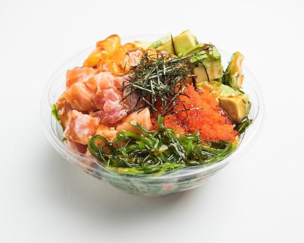 Close de uma salada de legumes com abacates em uma tigela de vidro em uma superfície branca