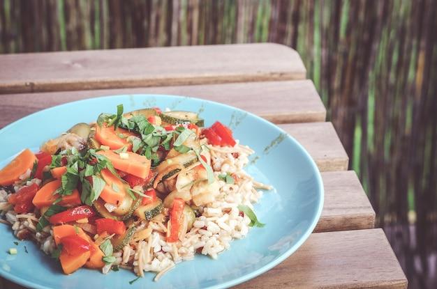Close de uma salada de legumes fresca com arroz em um prato de abobrinha