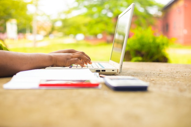 Close de uma senhora operando o laptop na porta