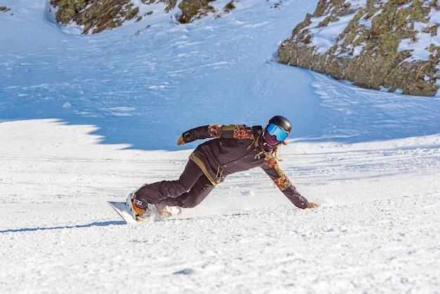 Close de uma snowboarder em movimento em uma prancha de snowboard em uma montanha