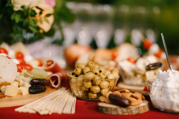 Close de uma tigela com azeitonas verdes sem caroço em uma mesa de buffet com produtos