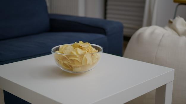 Close de uma tigela de batata frita colocada na mesa de woden em uma sala de festas vazia, sem ninguém dentro dela.