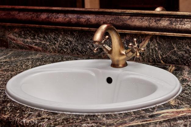 Close de uma torneira de latão com alças quentes e frias em uma pia branca em um banheiro