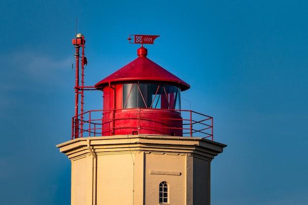 Close de uma torre vermelha e branca atrás de um céu azul