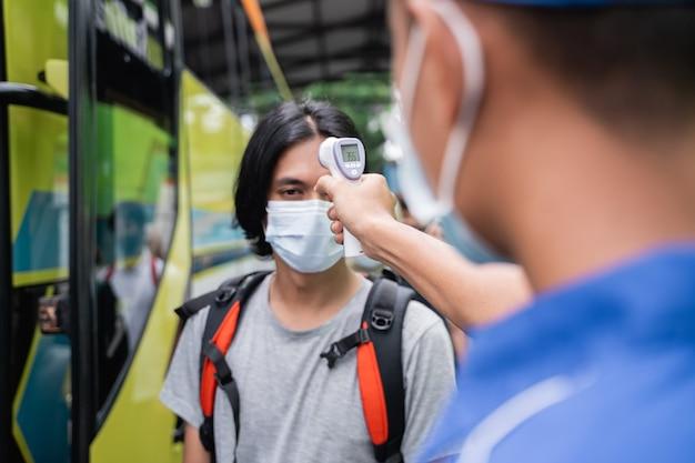 Close de uma tripulação de ônibus em uniformes azuis e um chapéu usando uma pistola térmica inspeciona o passageiro do sexo masculino na máscara antes de embarcar no ônibus
