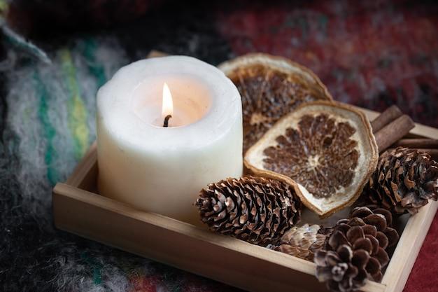 Close de uma vela queimando pinhas secas de laranjas e canela