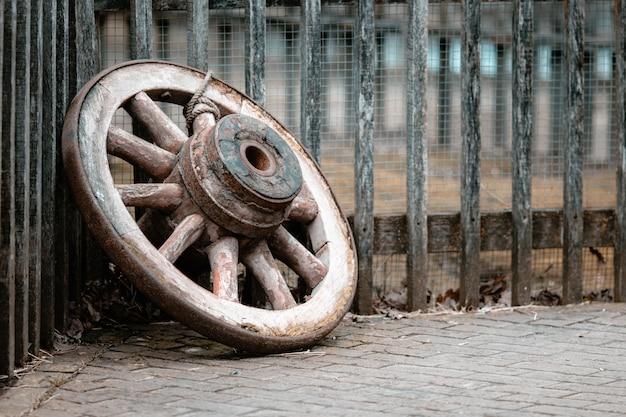 Close de uma velha roda de madeira no chão contra cercas sob as luzes
