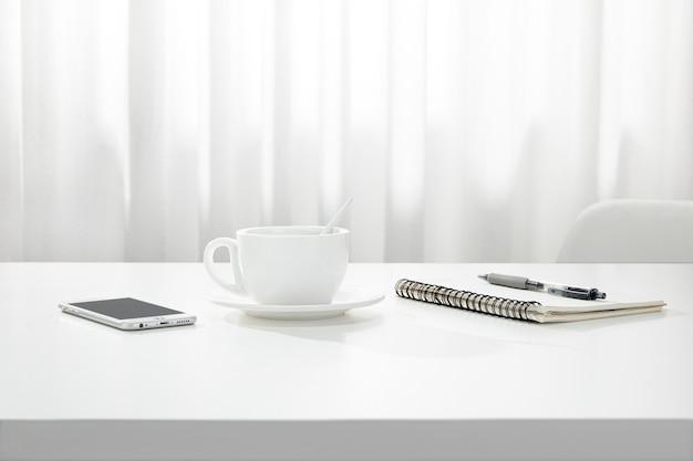 Close de uma xícara de café, um caderno e uma caneta e um smartphone em uma mesa branca, dentro de casa