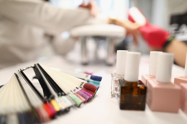 Close de várias cores apresentadas em tubos de vidro da paleta com cuidado profissional de esmalte