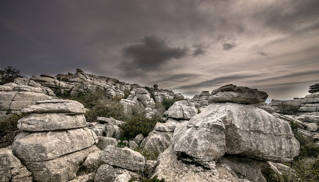 Close de várias pedras cinzentas umas em cima das outras sob um céu nublado