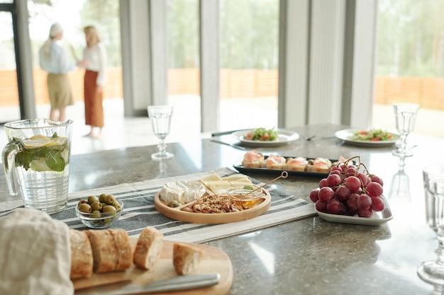 Close de vários petiscos como aperitivos, queijos e uvas na mesa de jantar