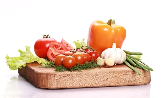 Close de vários vegetais frescos e saborosos em uma tábua de madeira
