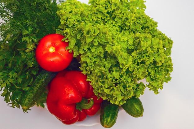 Close de vegetais para salada em uma tigela isolado