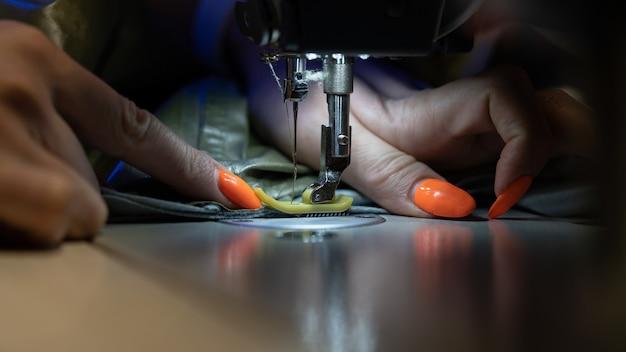 Close do alfaiate feminino trabalhando em padrões de tecido de ponto de máquina de costura para a indústria de vestuário
