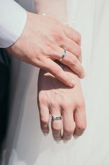 Close do anel recém-casados, o noivo toca suavemente a mão da noiva, marido e mulher, de mãos dadas v ...