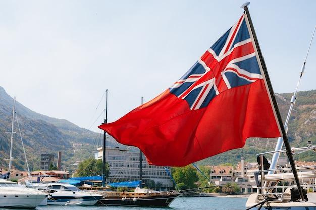 Close do british red ensign a bordo de um navio com navios e montanhas