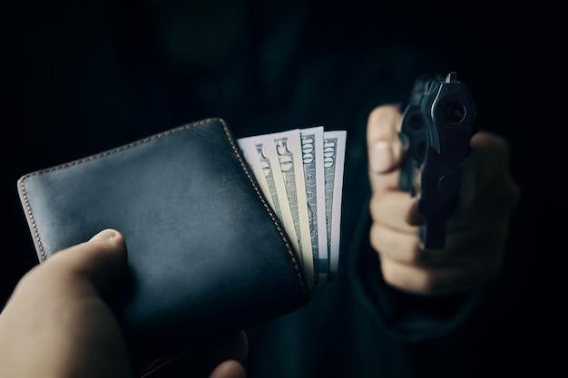Close do cano da arma e da bolsa com dinheiro assalto à mão armada assalto com pistola em homem desarmado.