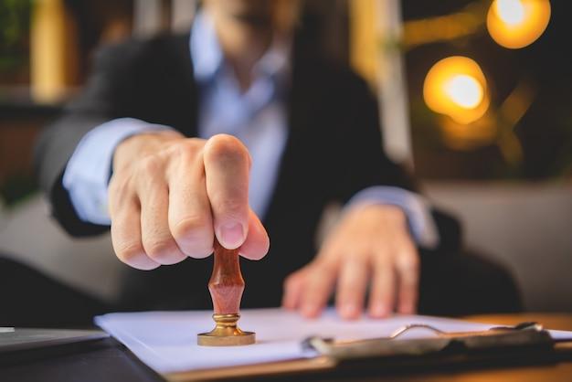 Close do carimbo da mão de uma pessoa com o carimbo aprovado no documento de certificado de aprovação, papel público em escrivaninha, tabelião ou empresário trabalhando em casa, isolado para proteção contra coronavírus covid-19