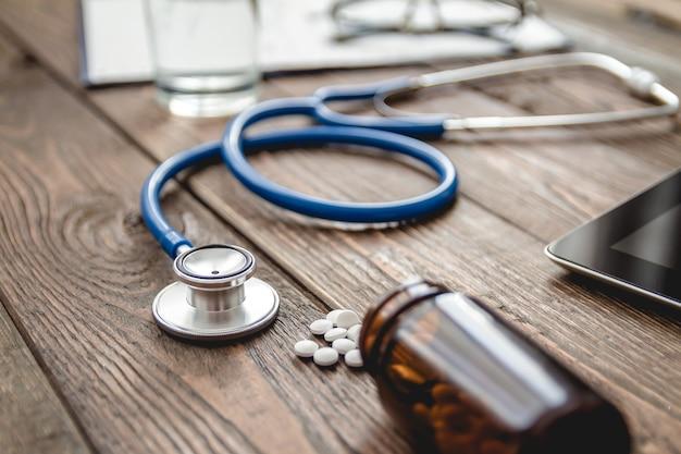 Close do cartão médico do paciente, um estetoscópio e comprimidos na mesa do médico
