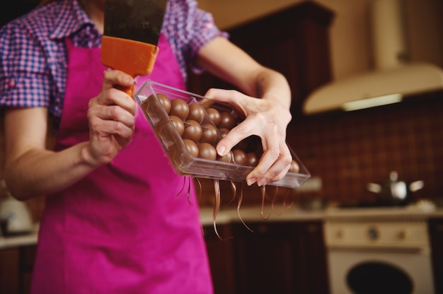 Close do chocolatier fazendo cascas para bombons de chocolate e removendo o excesso de chocolate dos moldes.
