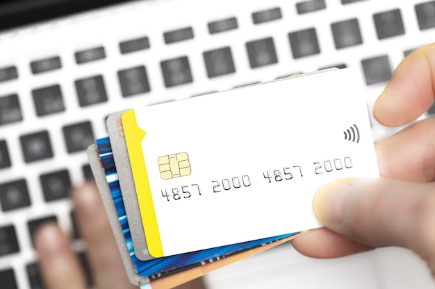 Close do comprador online pagando com cartões de crédito no teclado do computador com espaço de cópia