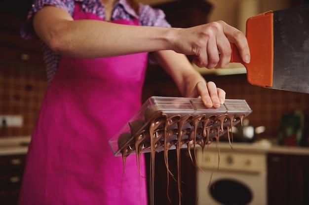 Close do confeiteiro fazendo cascas para bombons de chocolate e removendo o excesso de chocolate dos moldes.