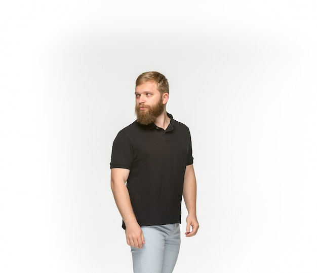 Close do corpo do jovem em t-shirt preta vazia no branco.