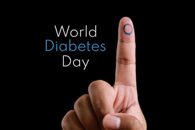 Close do dedo indicador de um jovem asiático com um círculo azul, símbolo da diabetes, em seu dedo indicador, e o texto dia mundial da diabetes sobre fundo preto