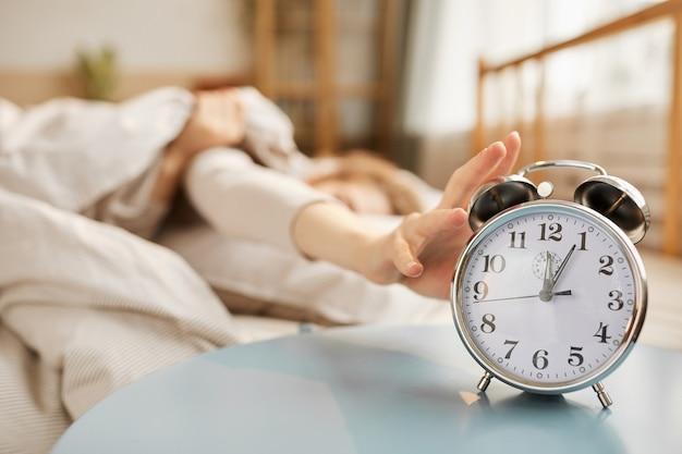 Close do despertador tocando na mesa com uma mulher dormindo na cama, na parede