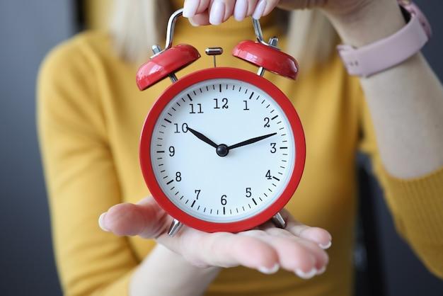 Close do despertador vermelho nas mãos de uma mulher
