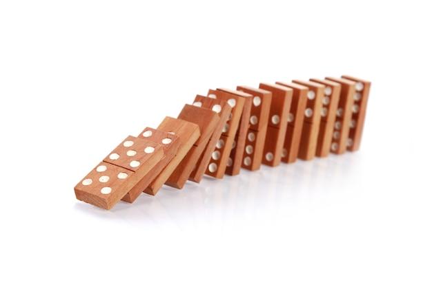 Close do dominó de madeira caindo sobre uma superfície branca