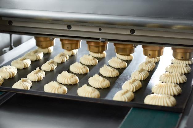 Close do equipamento da linha de transporte, fazendo pequenos bolos idênticos com massa crua. eles ficam no prato preto na esteira rolante da padaria.