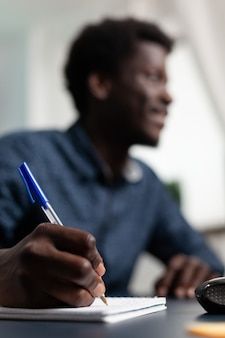 Close do estudante negro escrevendo estratégia financeira no caderno