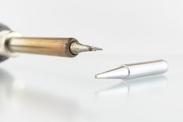 Close do ferro de soldar em um fundo de mesa de vidro