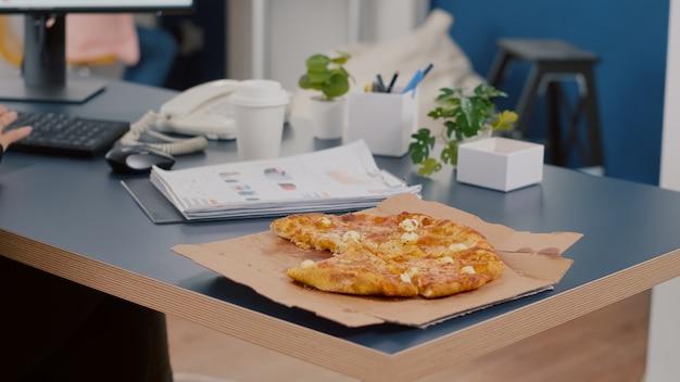Close do gerente executivo pegando uma fatia de pizza comendo na frente do computador digitando gráficos financeiros no escritório da empresa de inicialização