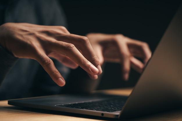 Close do hacker está usando o laptop para codificar vírus ou malware para hackear.