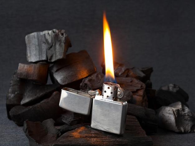 Close do isqueiro de metal com fogo ardente no fundo de carvão escuro com reflexos