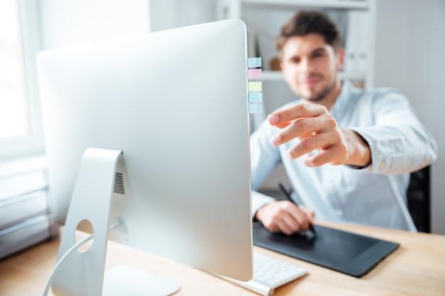 Close do jovem designer colocando adesivos no monitor do computador e usando a mesa gráfica no escritório