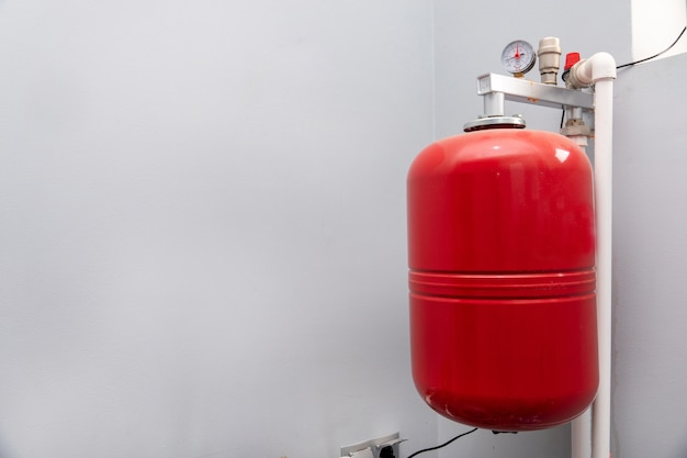 Close do manômetro, tubos e válvulas de torneira do sistema de aquecimento em uma sala de caldeira