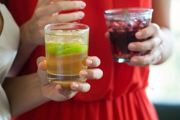 Close do meio de uma mulher segurando bebidas no restaurante